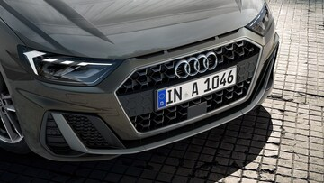 The wide track and short overhangs of the all-new Audi A1 Sportback provide for a taut, sporty look. The wide, low-placed Singleframe grille and the implied side air inlets dominate the distinctive front. Overseas model with optional equipment shown.